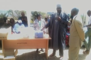 Representative of the Permanent Secretary Dr.Olaniran Alabi (middle) being assisted by a Director in the ministry, Dr. Dooshima Kwange (left) to present  materials to one of the beneficiaries