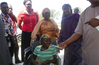 Executive Director of ISMPH,Mrs Moji Makanjuola and the Chairperson of Karshi Development Area Council, Barrister Fatimah Assibi-Ubam pushing Ramatu on her wheelchair