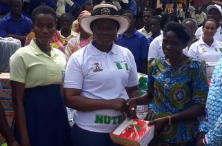 Spouse of the Nigerian High Commissioner to Ghana, Mrs. Margaret Kikelomo Abikoye presenting one of the items  to the Headmistress of School of the Deaf, Dumb and Blind   Akuapim Mampong ,Mrs. Mahela Narh